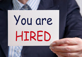 You are hired - Businesswoman with sign