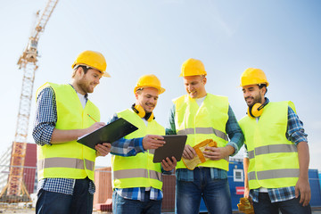group of smiling builders with tablet pc outdoors