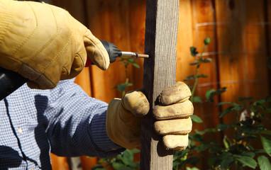 Man drills into piece of wood