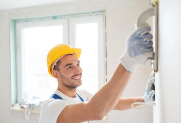 smiling builder working with grinding tool indoors
