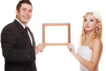 wedding couple with empty frame for photos.