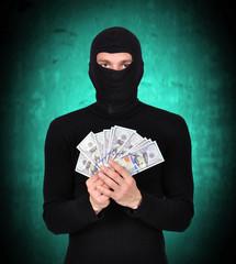 man in mask holding dollars