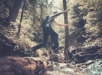 Man hiker jumping across stream in mountain forest