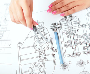 Female architect working with blueprints at office desk.