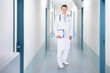 Confident Doctor Holding Clipboard On Corridor In Hospital