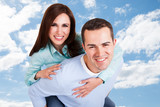 Happy Man Giving Piggyback Ride To Girlfriend Against Sky