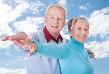 Senior Couple With Arms Outstretched Standing Against Cloudy Sky