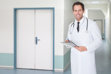 Confident Doctor Holding File In Hospital Corridor