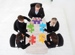 Businesspeople With Jigsaw Pieces Sitting At Table