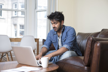Asian man at home using a laptop.