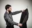 Handsome man with beard choosing jacket
