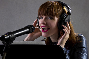 stylish female singer with microphone and reading lyrics
