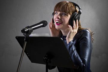 stylish female singer with microphone and reading lyrics