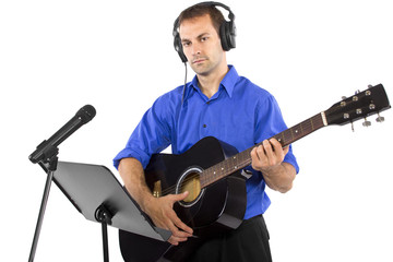 male singer holding a guitar and wearing headphones