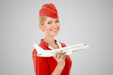 Charming Stewardess Holding Airplane In Hand. Gray Background.