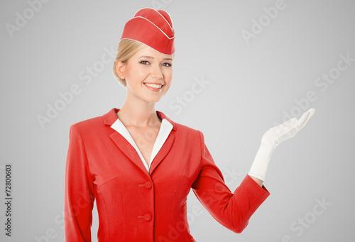 Leinwanddruck Bild Charming Stewardess Dressed In Red Uniform Holding In Hand On Gr