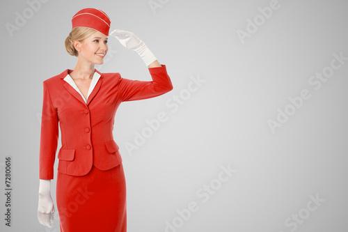 Leinwandbild Motiv Charming Stewardess Dressed In Red Uniform On Gray Background.