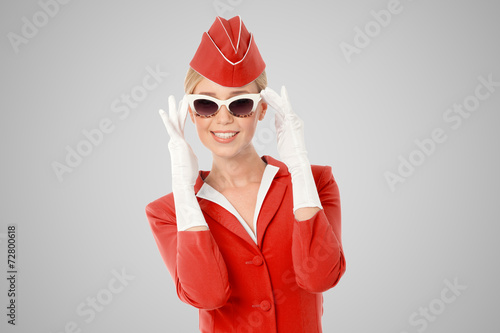 Charming Stewardess Dressed In Red Uniform And Vintage Sunglasse - 72800618