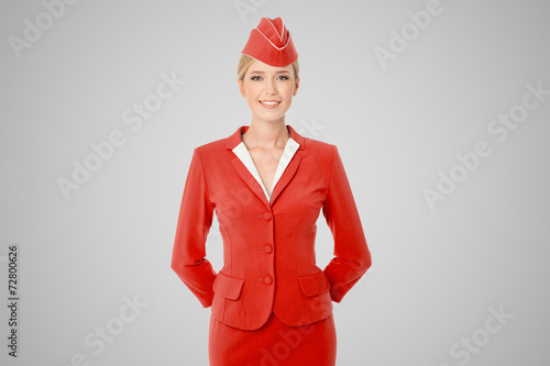 Charming Stewardess Dressed In Red Uniform On Gray Background. - 72800626