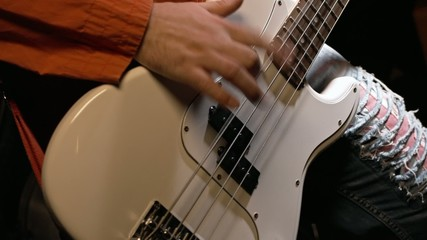 A young man plays on a white bass guitar