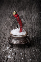 sea ​​salt in a large antique salt shaker and hot red pepper