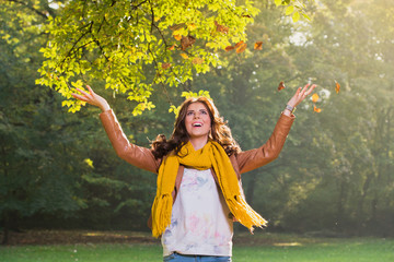 Beautiful young woman throwing leaves in the park
