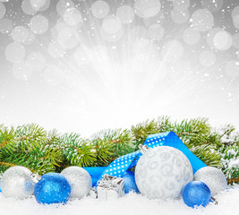 Christmas baubles and blue ribbon with snow fir tree