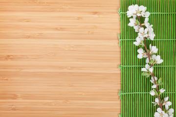 Sakura branch over bamboo mat