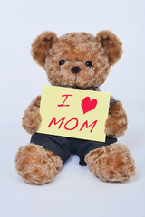 Teddy bear holding a yellow sign that says I love mom