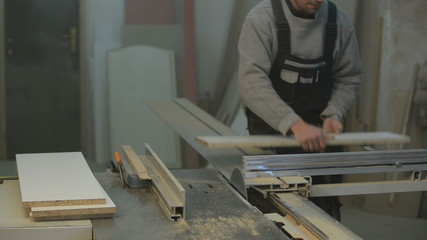 carpenter cutting the wooden panel with circular saw