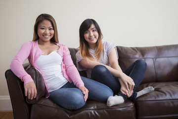 Two Asian women sitting on sofa at home.