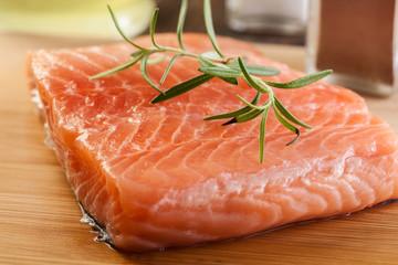 Raw salmon filet on wooden cutting board