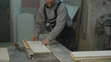 arpenter cutting the wooden panel with circular saw