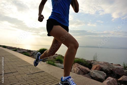 Fototapeta woman runner athlete running at sunrise seaside