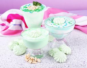Mint milk dessert in glass bowls on color wooden background