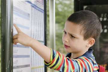Child  reading timetable at  bus stop
