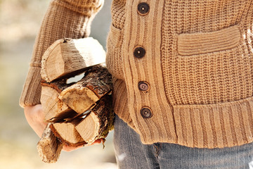 man's hand hold firewoods in brown sweater in autumn forest