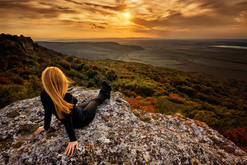 A woman enjoys the view of sunset over an autumn forest