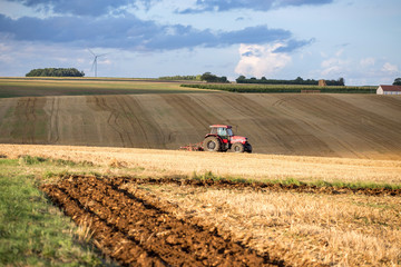 Red tractor harrowing a field. France