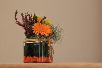 Hintergrund mit Blumen im dekorativen Glas