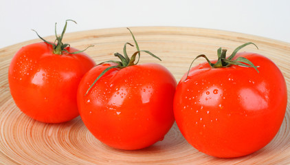 Fresh red tomatoes on wooden plate