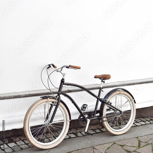 Staande foto Fiets Cruiser bicycle near a white wall