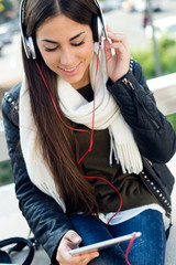 Beautiful girl listening to music in city.