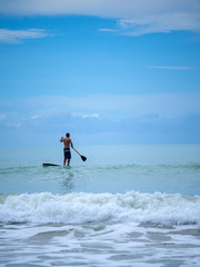 Man Stand up paddle surfing in Thailand