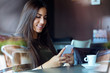 Beautiful girl using her mobile phone in cafe. - 72821478
