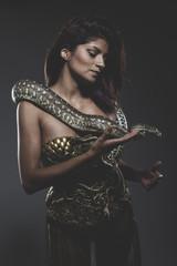 Sensual tattooed woman with big snake and iron corset