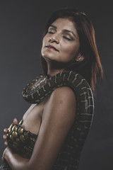Sensual tattooed woman with big snake and iron corset