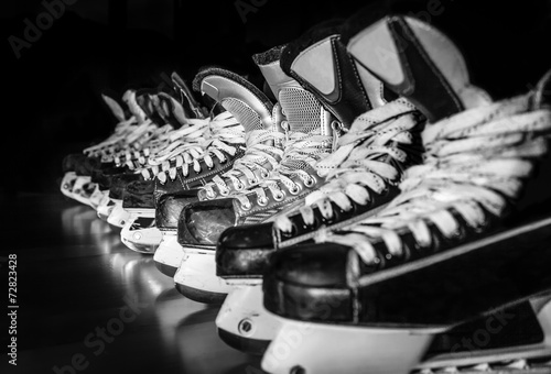 Hockey skates lined up in locker room Poster