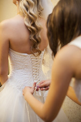 girlfriend tying corset bride on wedding