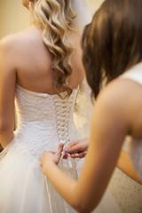 girlfriend tying corset bride on wedding